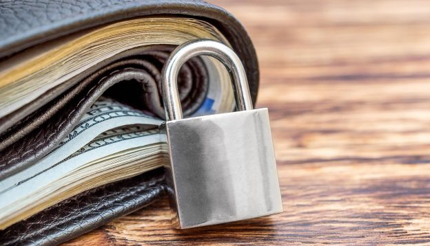 Padlock and wallet with money showing FinCEN rules on crypto wallets